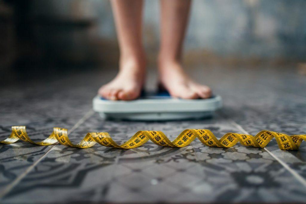 donna su bilancia e metro per misurare circonferenza vita