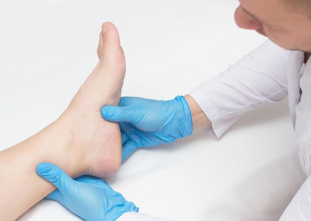medico esamina paziente dolore tallone epianta del piede